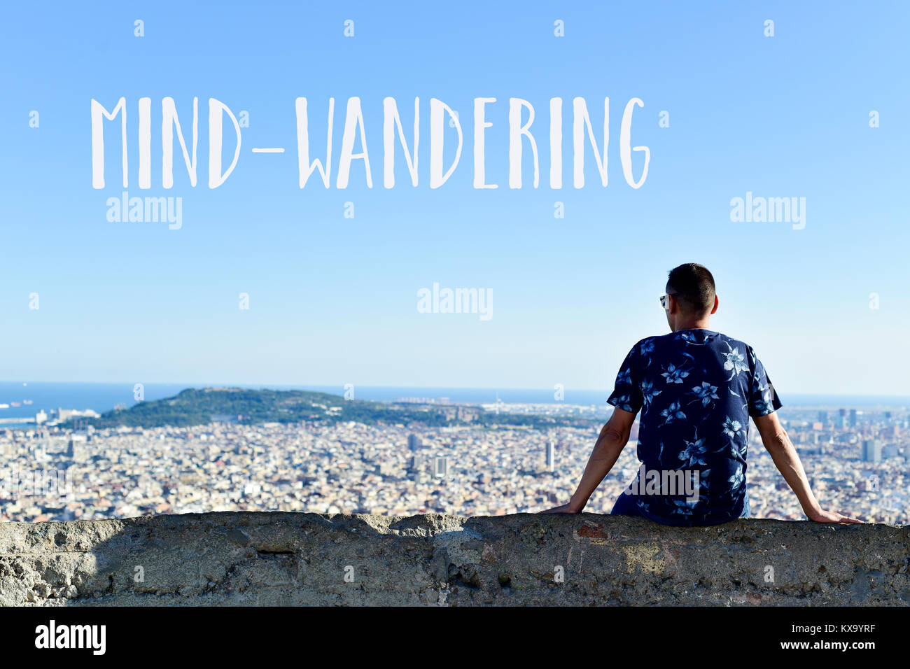 the text mind-wandering and a young caucasian man, seen from behind, at the top of a hill observing the city and - Stock Image