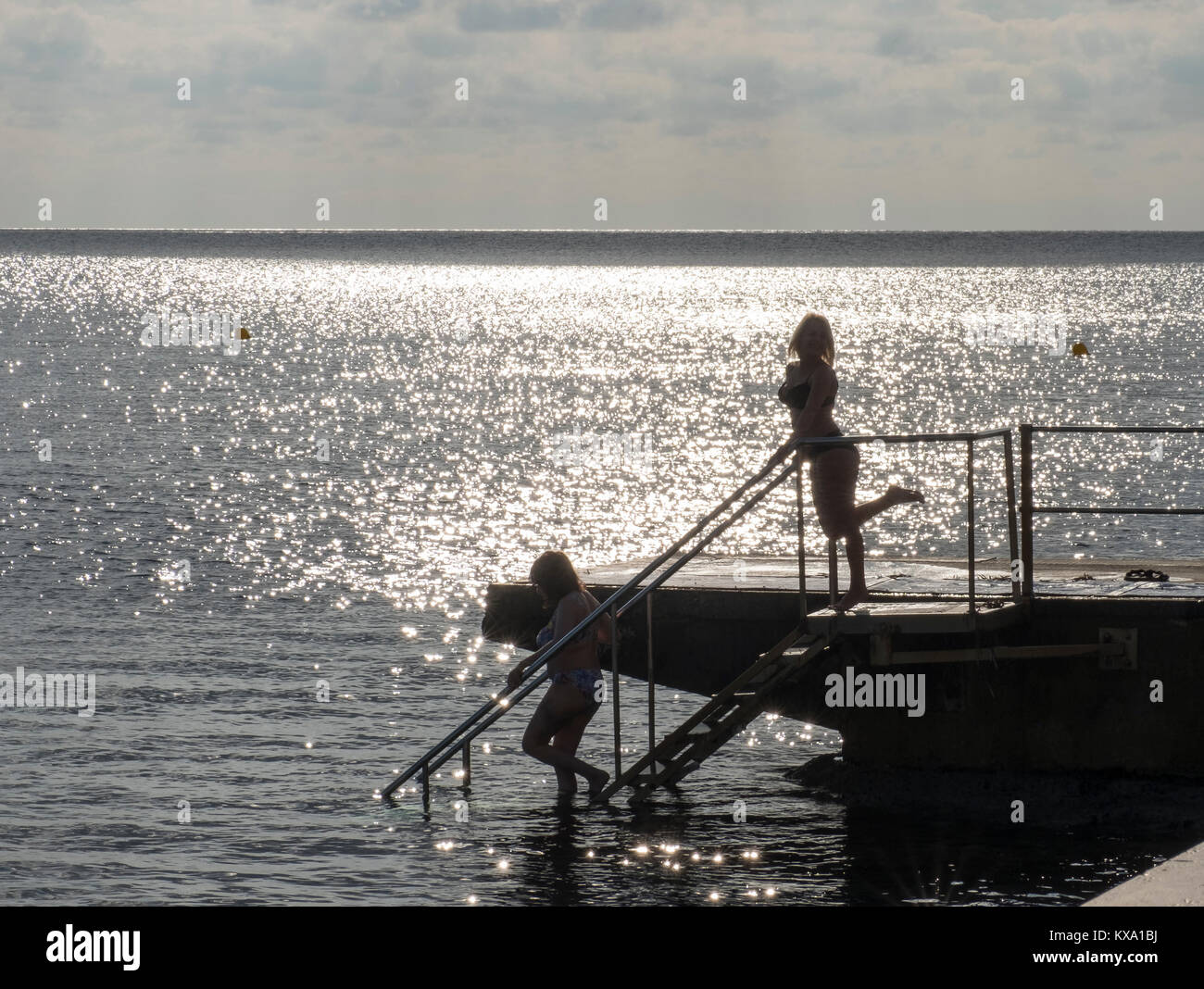 Two female swimmers in silhouette enter the water on Kato Paphos seafront, Paphos, Cyprus. - Stock Image