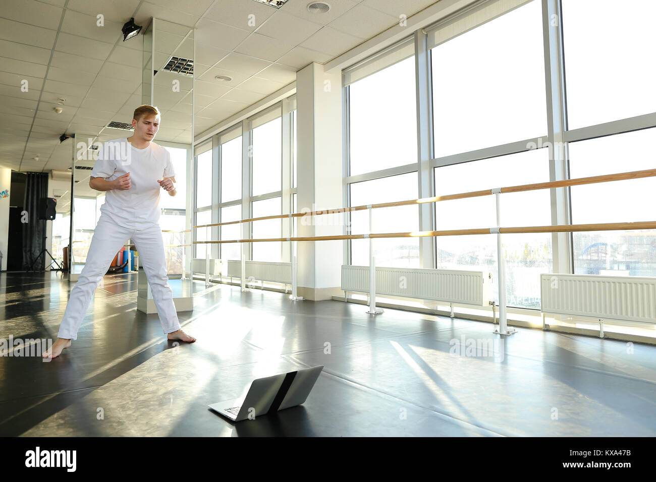 Male person learning new movements with laptop at gym. - Stock Image