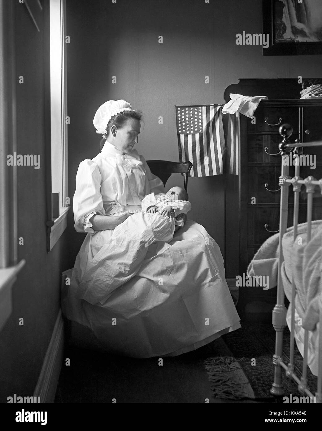 Mother with newborn baby in bedroom. The US Flag with 46 stars was in use from  July  4, 1908 to  July 3, 1912. - Stock Image