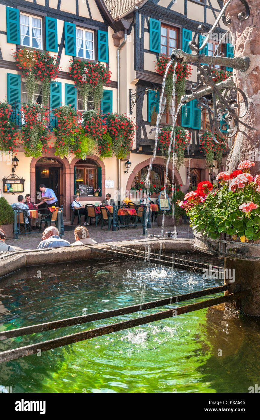 Kaysersberg Alfresco Bar Restaurant Waiter Alsace France Fountain in central square with restaurant Hotel Du Chateau - Stock Image