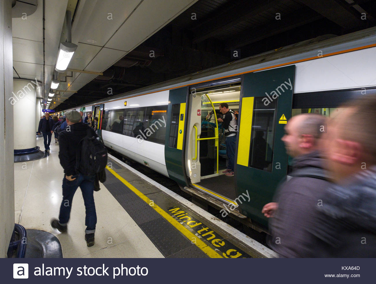 People walking on train platform past train in Victoria Station, City of Westminster, London, England, United Kingdom - Stock Image