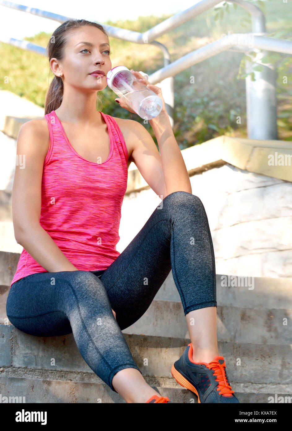 Sporty woman drinking water outdoor on sunny day. Fitness and healthy lifestyle concept Stock Photo
