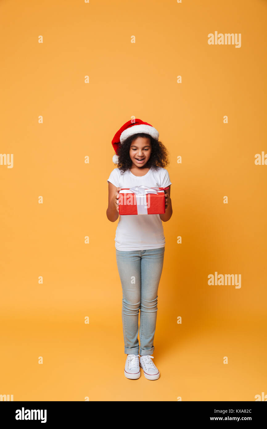 Picture of surprised african pretty little girl wearing santa christmas hat holding gift box in hands. Looking aside. - Stock Image