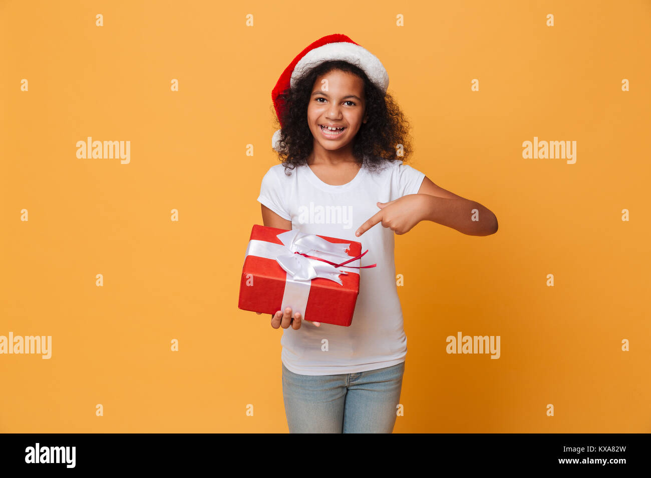 Image of happy african pretty little girl wearing santa christmas hat holding gift box in hands. Looking camera - Stock Image