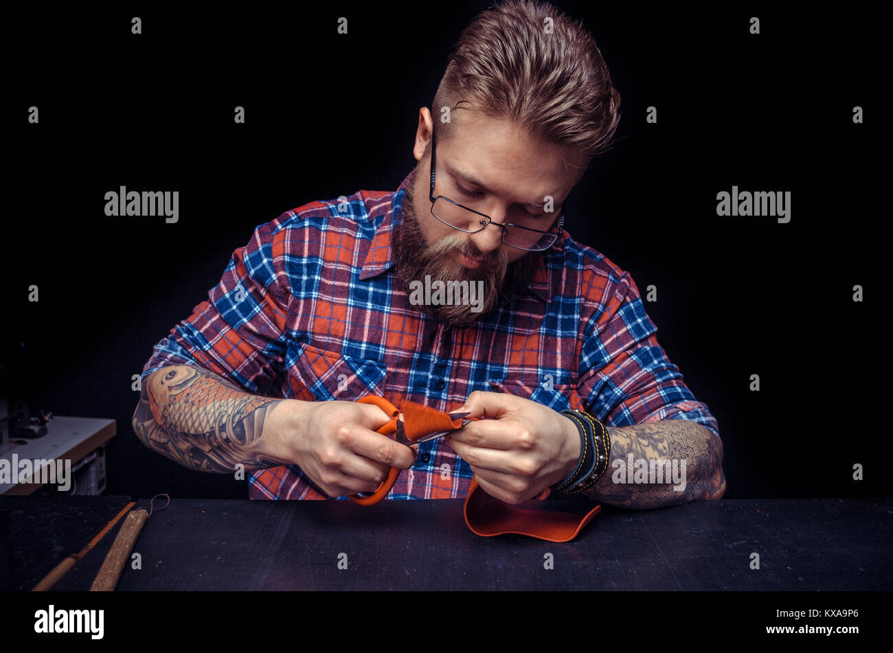 Leather Professional creating new leatherwork - Stock Image