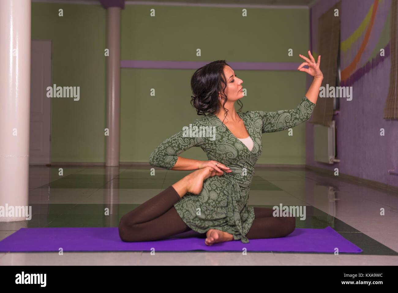Fit girl performs yoga asana in a studio Stock Photo