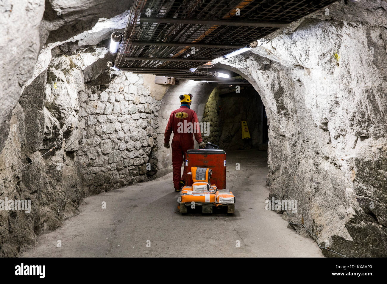 Worker carrying cement on electric pallet truck in of tunnels of Aiguille du Midi, Chamonix Mont-Blanc, Haute Savoie, Stock Photo