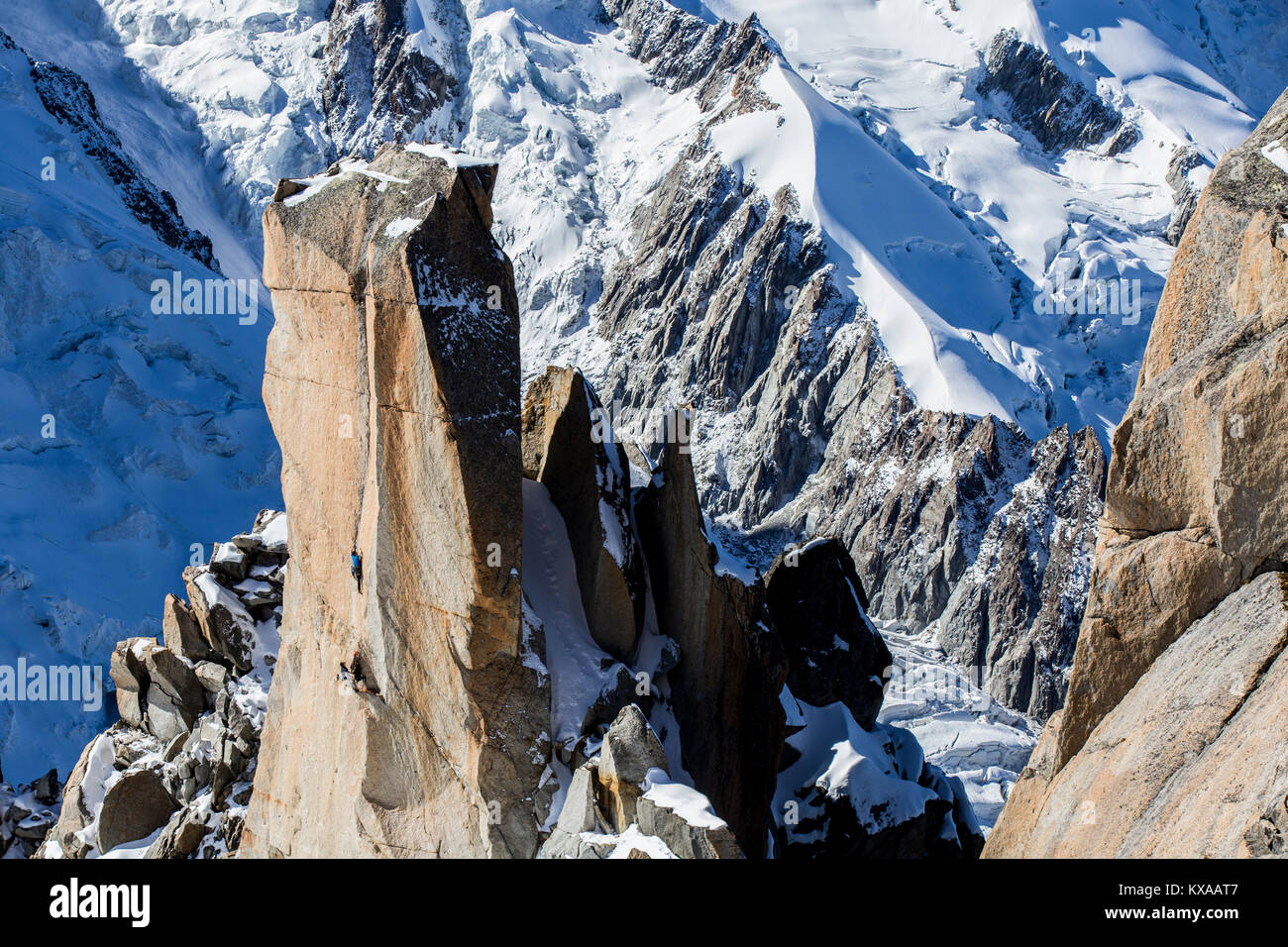 Two alpinists climbing rock pillar below Aiguille du Midi in French Alps, Chamonix Mont-Blanc, Haute Savoie, France - Stock Image