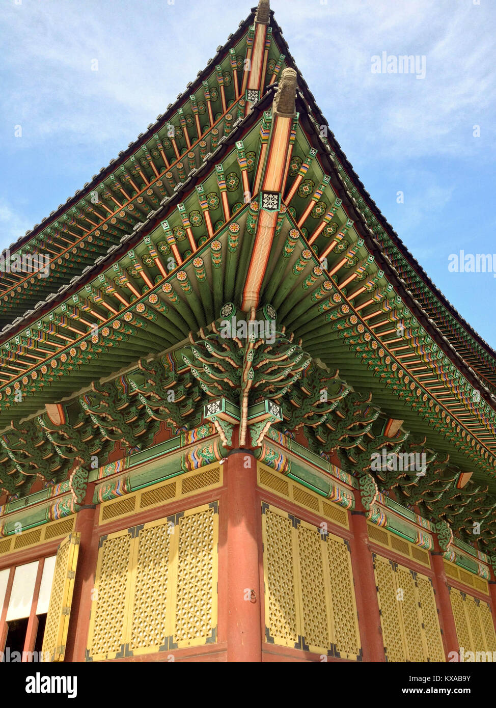 Partial view of the colorful Gyeongbokgung Palace with ornate wooden details layered roof line and other architectural - Stock Image