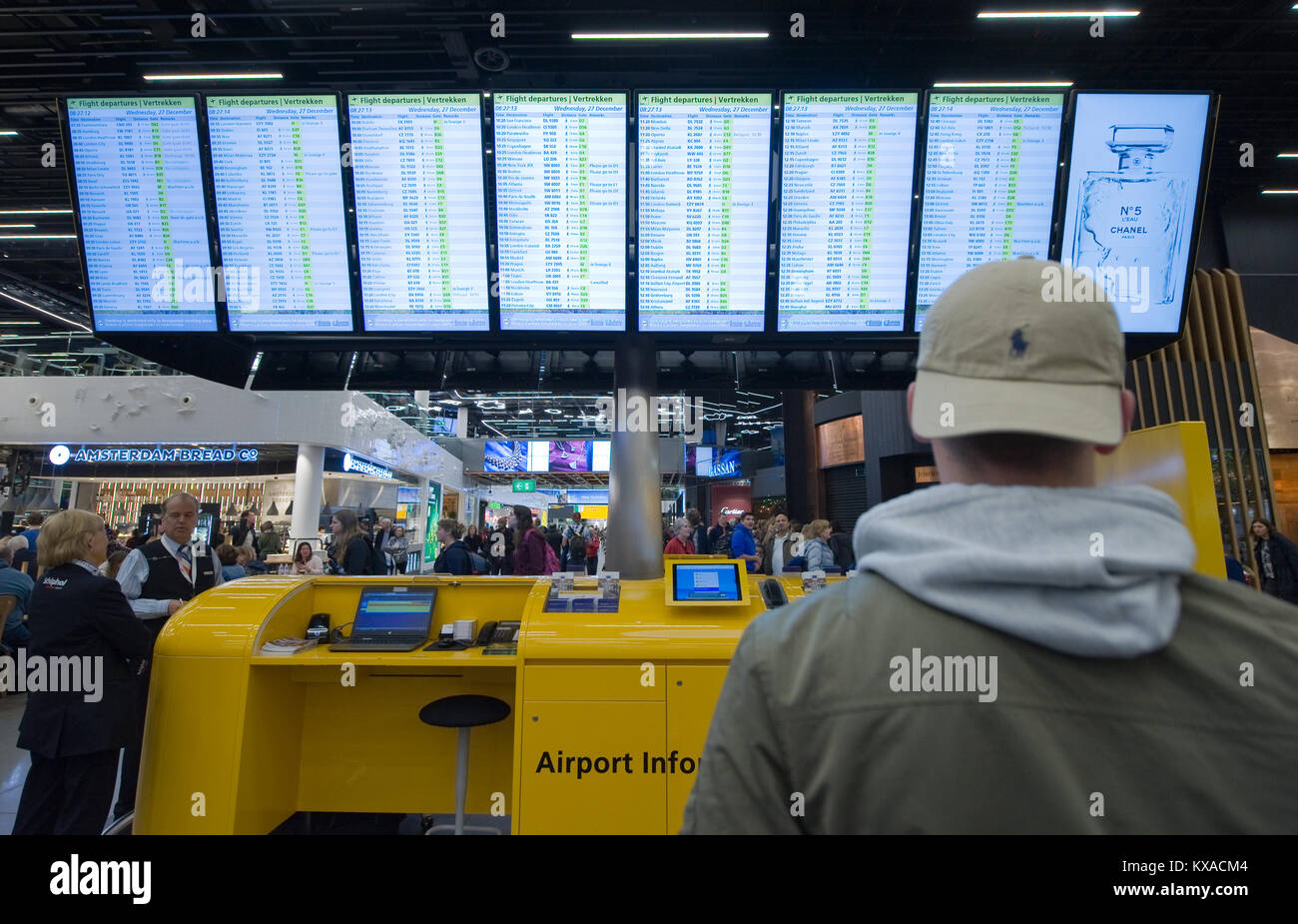 AMSTERDAM, NETHERLANDS - DEC 27, 2017: A man is looking at the information screens to check his flight on Schiphol - Stock Image