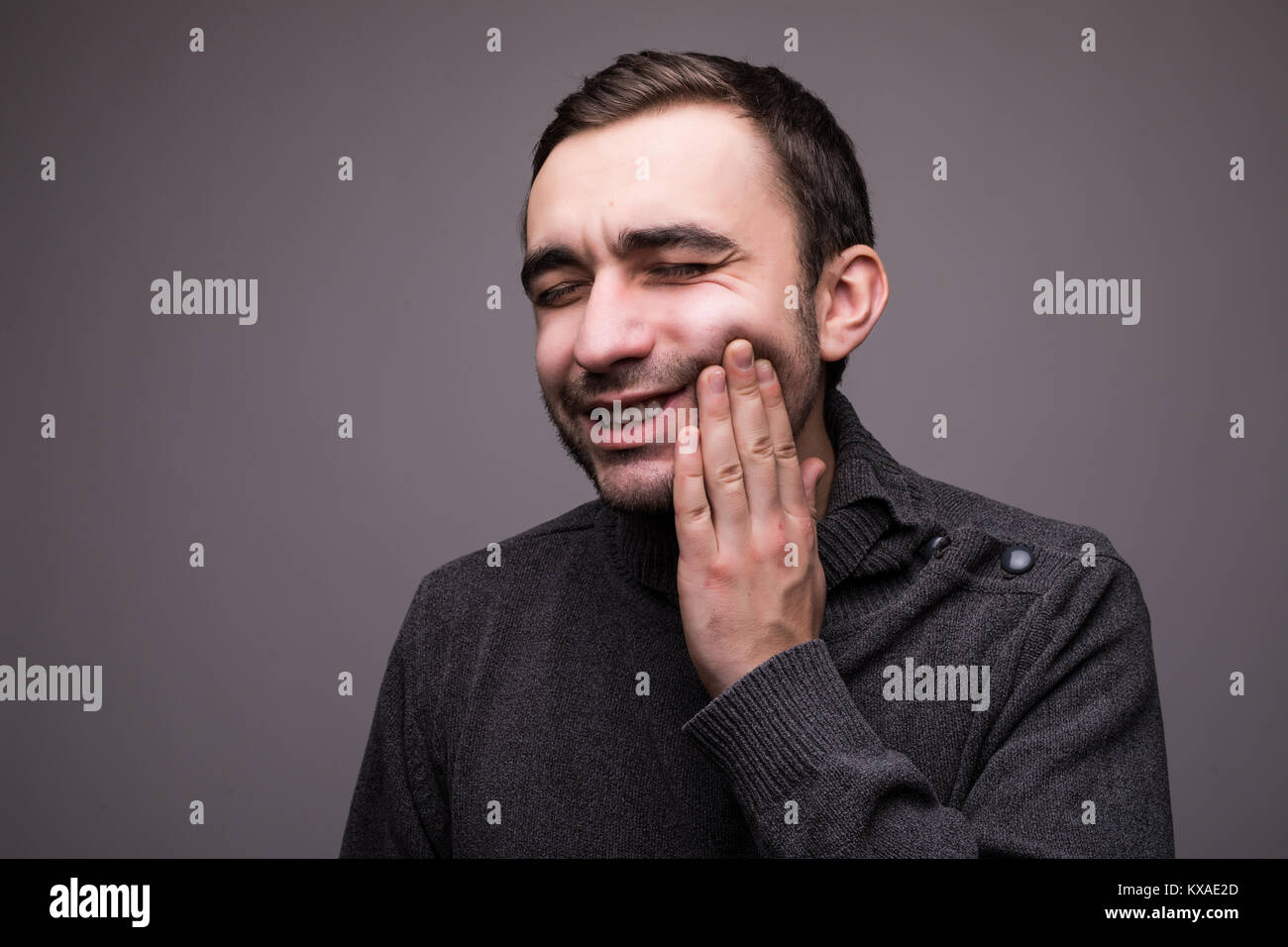 Closeup portrait of young man with tooth ache crown problem about to cry from pain touching outside mouth with hand, - Stock Image