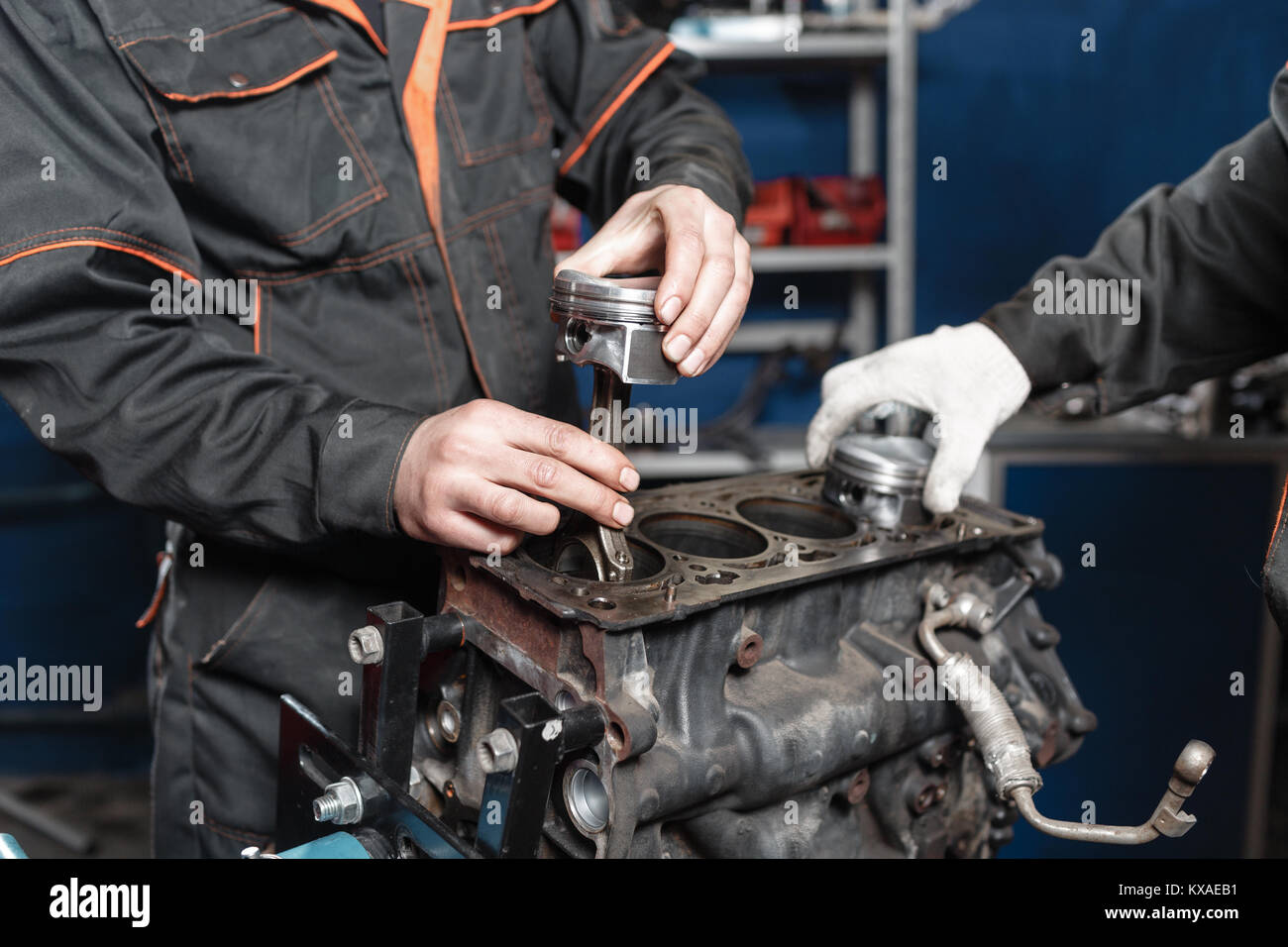 the mechanic installs a new piston. Disassemble engine block vehicle. Motor capital repair. Sixteen valves and four - Stock Image