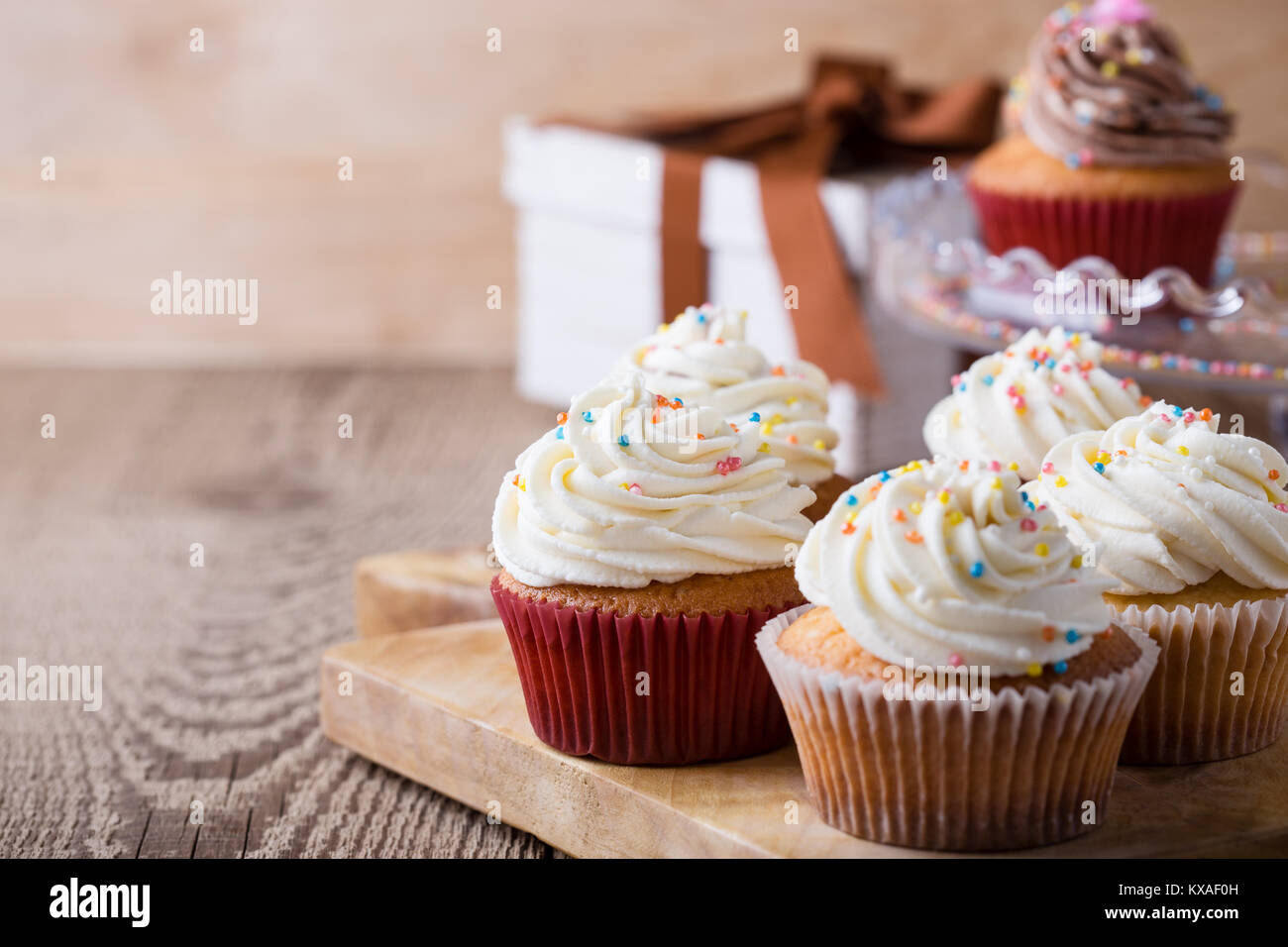 Delicious birthday cupcakes on wooden table - Stock Image