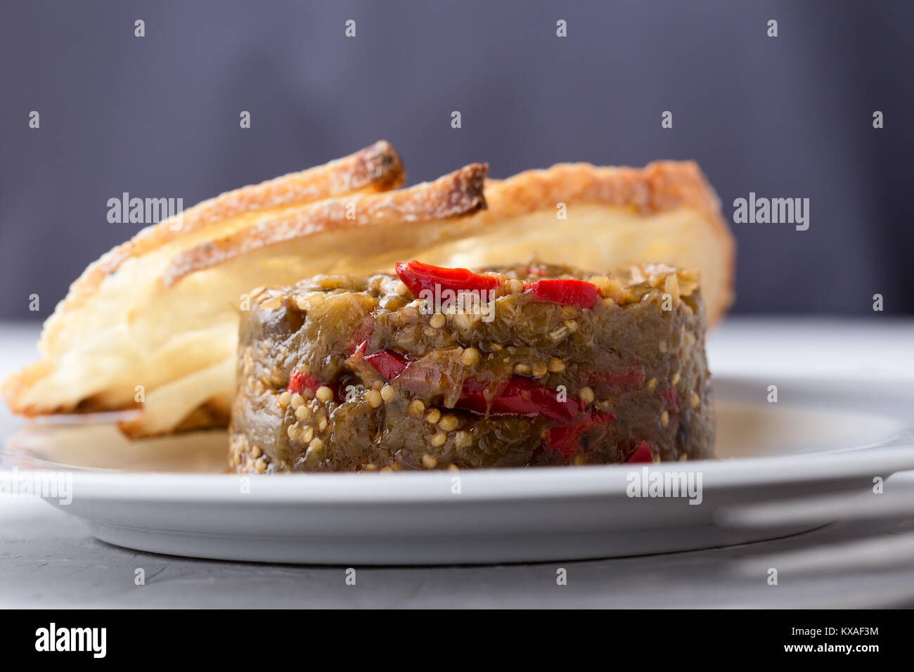 Appetizer of eggplant and red bell pepper, vegetable dip served with toasted bread on white plate Stock Photo