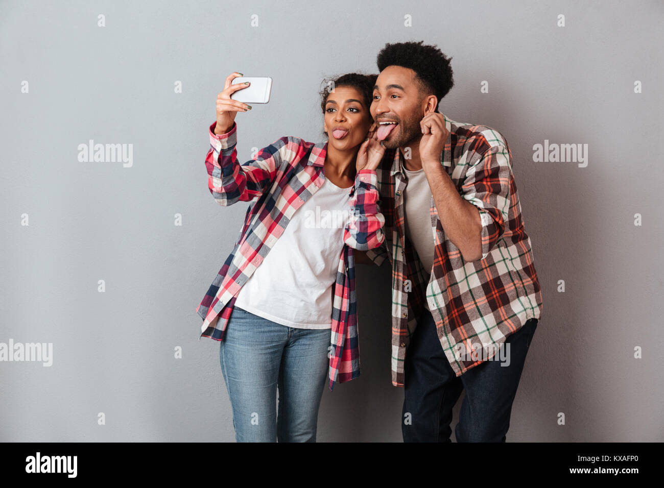 Portrait of a happy young african couple grimacing while standing together and taking a selfie isolated over gray - Stock Image