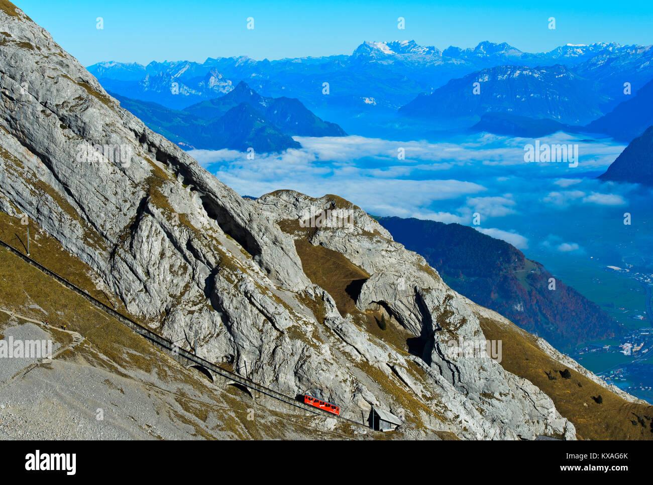 Red wagon of the Pilatus Railway at Mount Pilatus,mountain panorama in the background,Alpnachstad,Switzerland - Stock Image