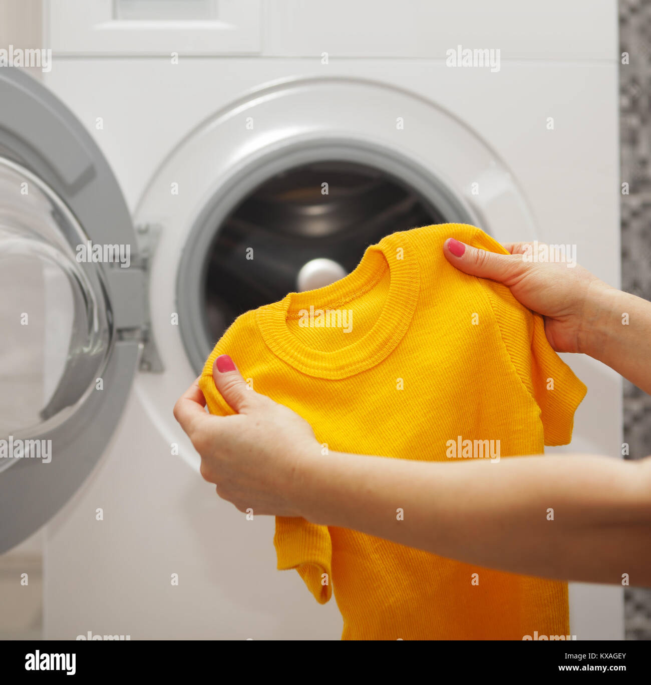 Knitted T-shirt in the hands of a woman who is going to wash it in washing mashine - Stock Image