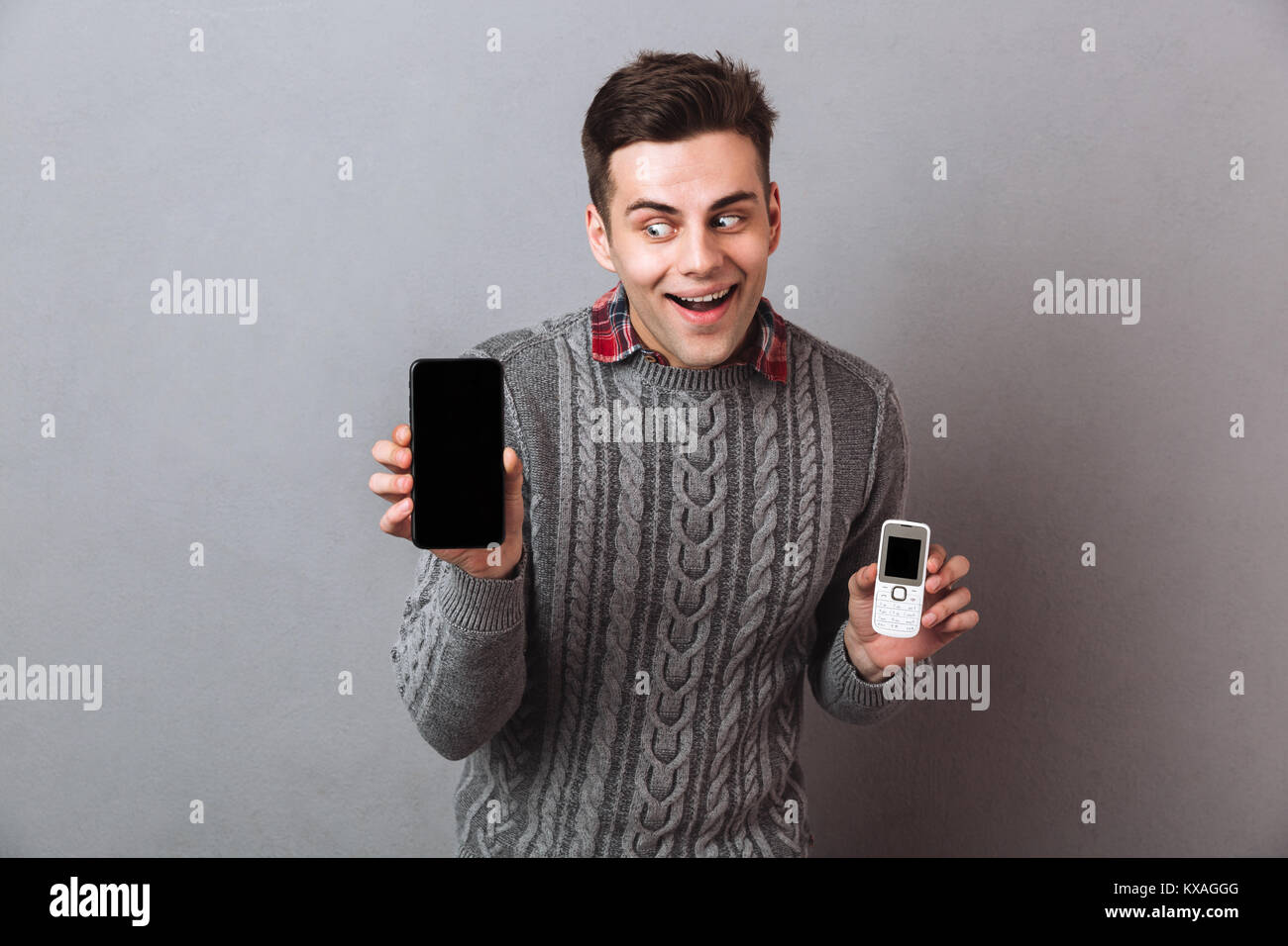 Intrigued man in sweater choosing between smartphones over gray background - Stock Image