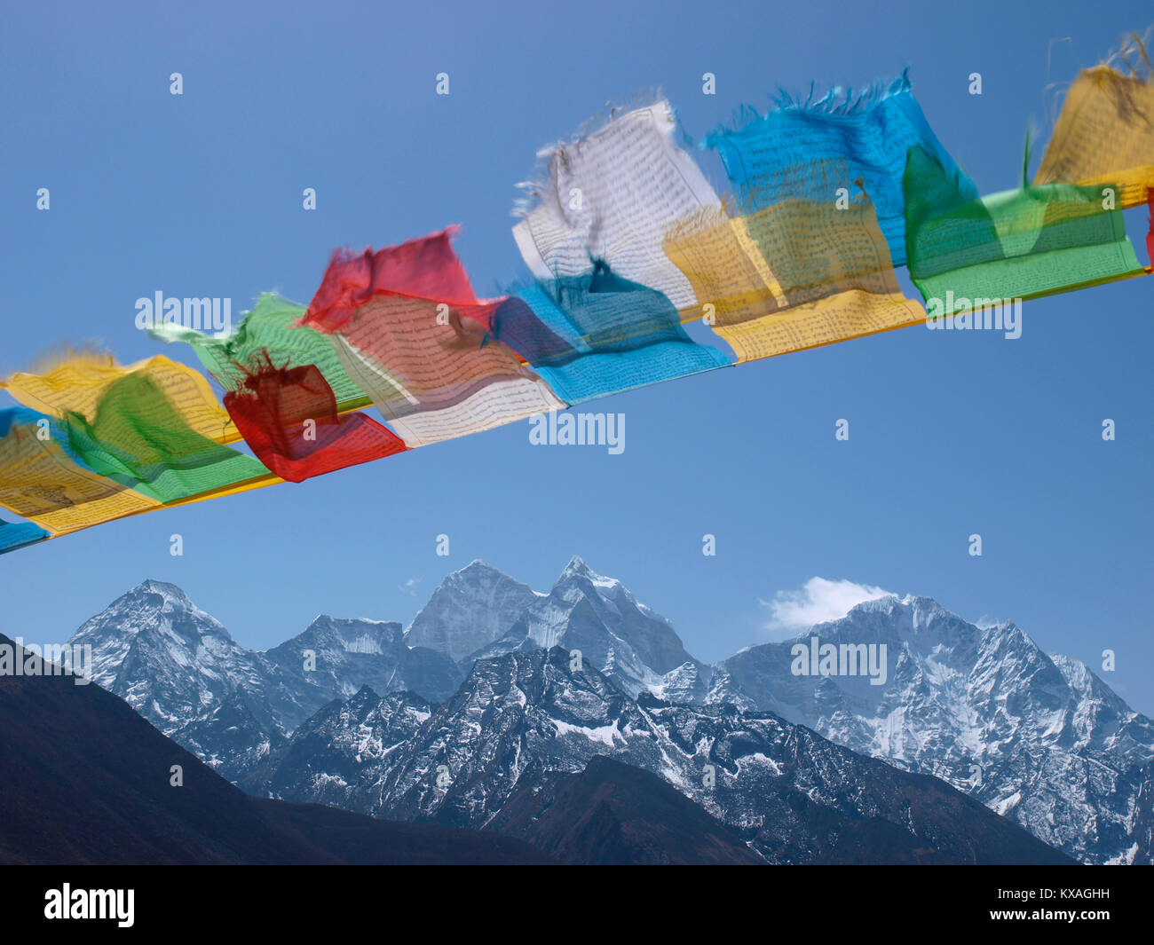 Buddhist prayer flags waving in wind Himalayan peaks of Mount Everest region in background, Lukla, Khumbu, Nepal - Stock Image