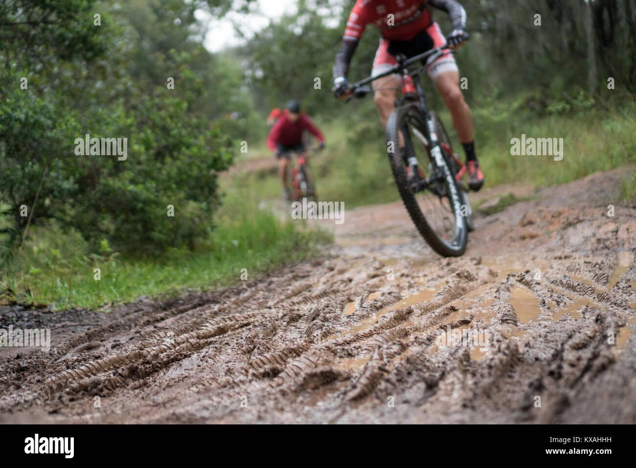 Two men riding mountain bikes on mud, Huasca de Ocampo, Hidalgo, Mexico - Stock Image
