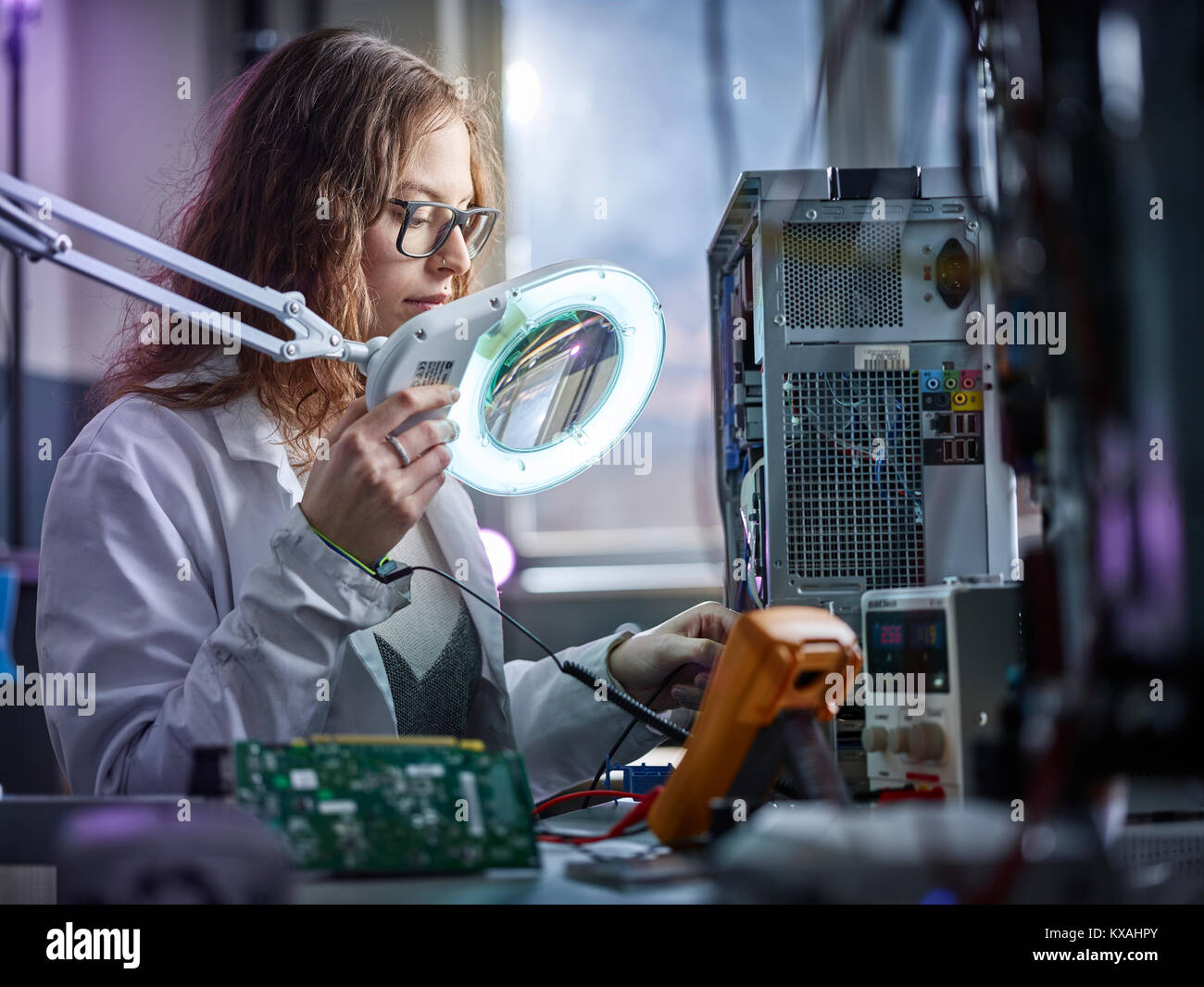 Technician with white lab coat with a measuring device in an electronics laboratory, Austria - Stock Image