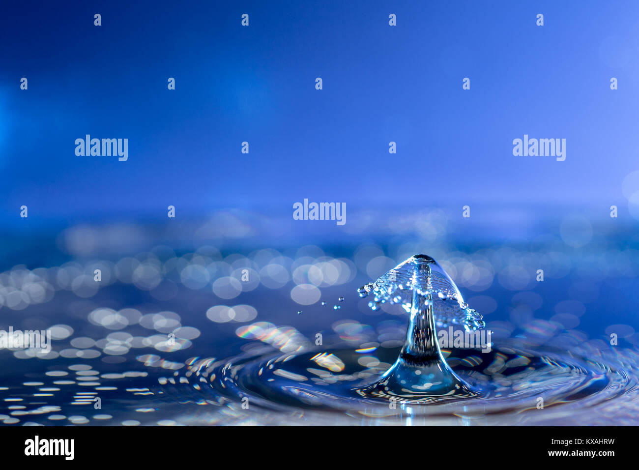 Photograph of Water droplets with a coloured background. also known as water droplet collision. - Stock Image