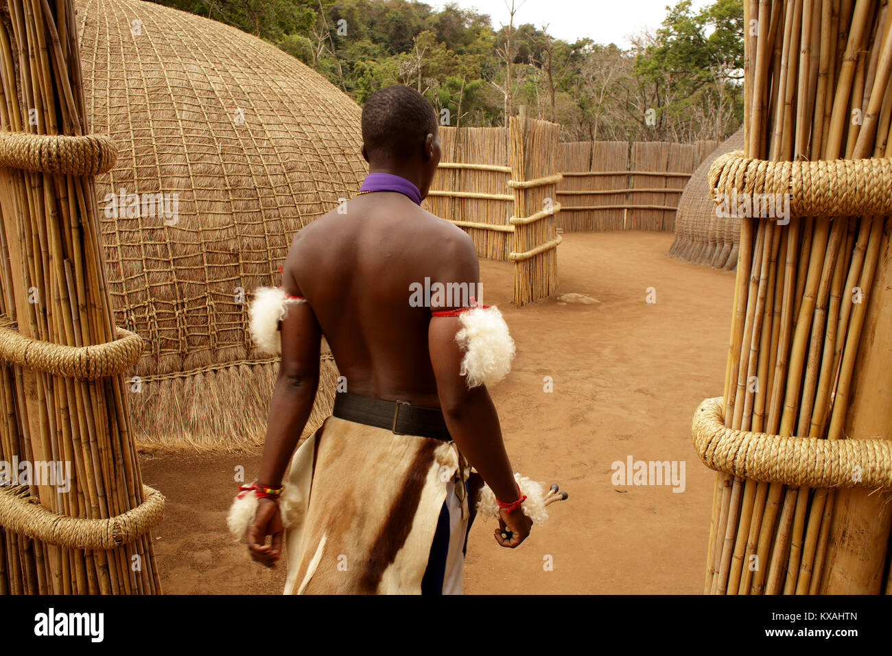 Native wearing traditional clothing walking across primitive village, Swaziland - Stock Image