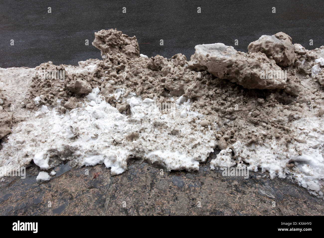 Dirty piles of snow on a street in New York City - Stock Image