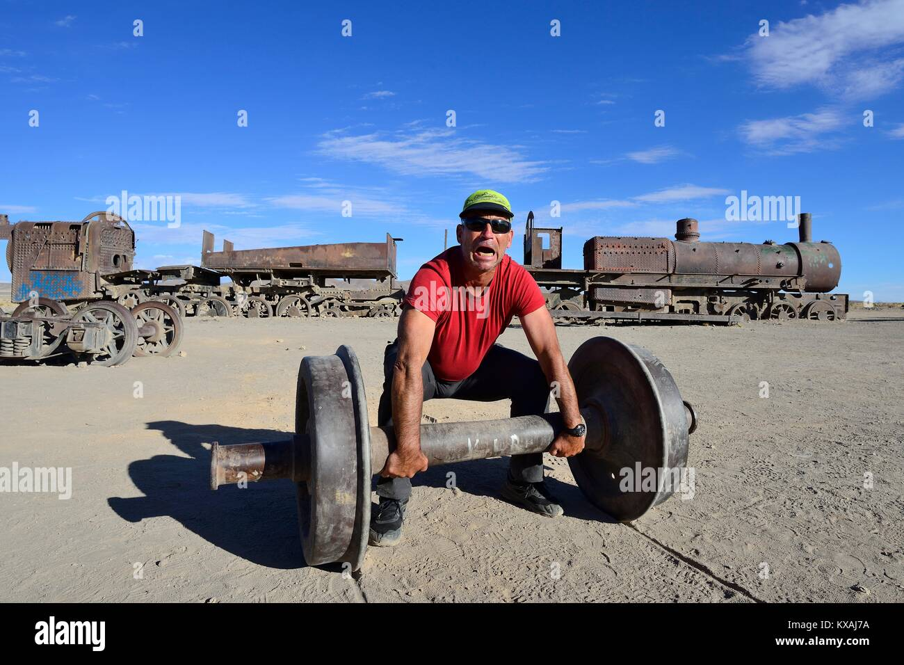 Tourist uses axle as barbell, railway cemetery, Uyuni, Potosi, Bolivia - Stock Image