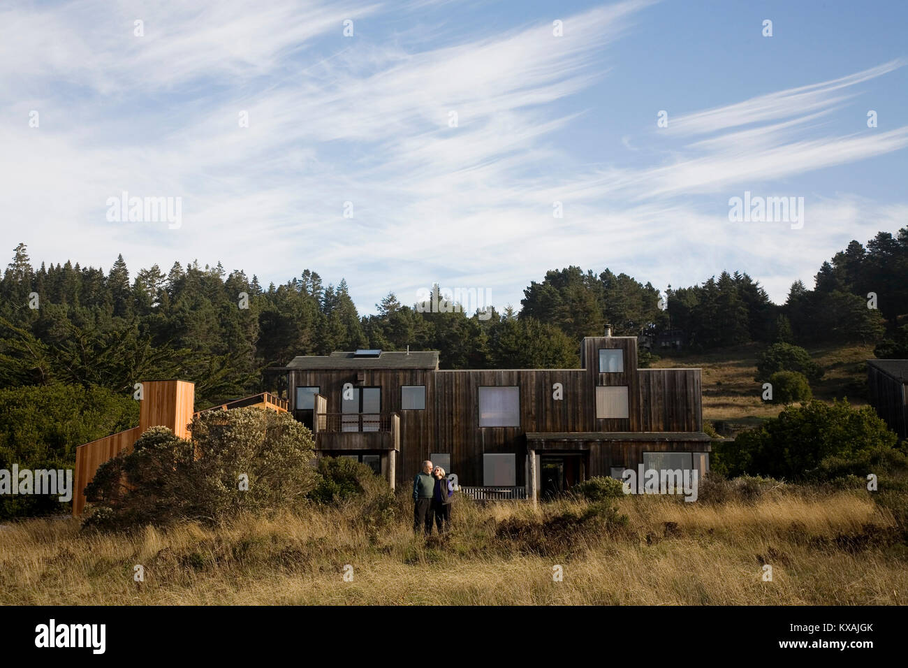 Couple standing outside modern house at sea ranch community mendocino california usa
