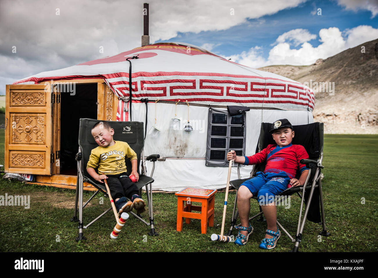 Young Mongol nomad boys sitting outside ger (yurt) tent, Bunkhan, Bulgan, Mongolia - Stock Image