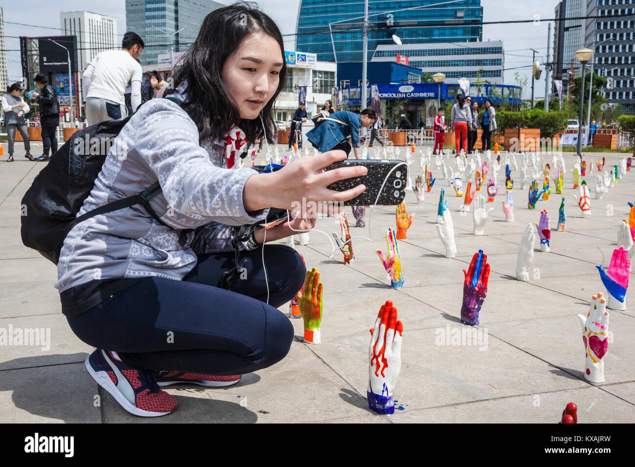 Mongol girl taking selfie with installation art in Ulaanbaatar, Mongolia - Stock Image