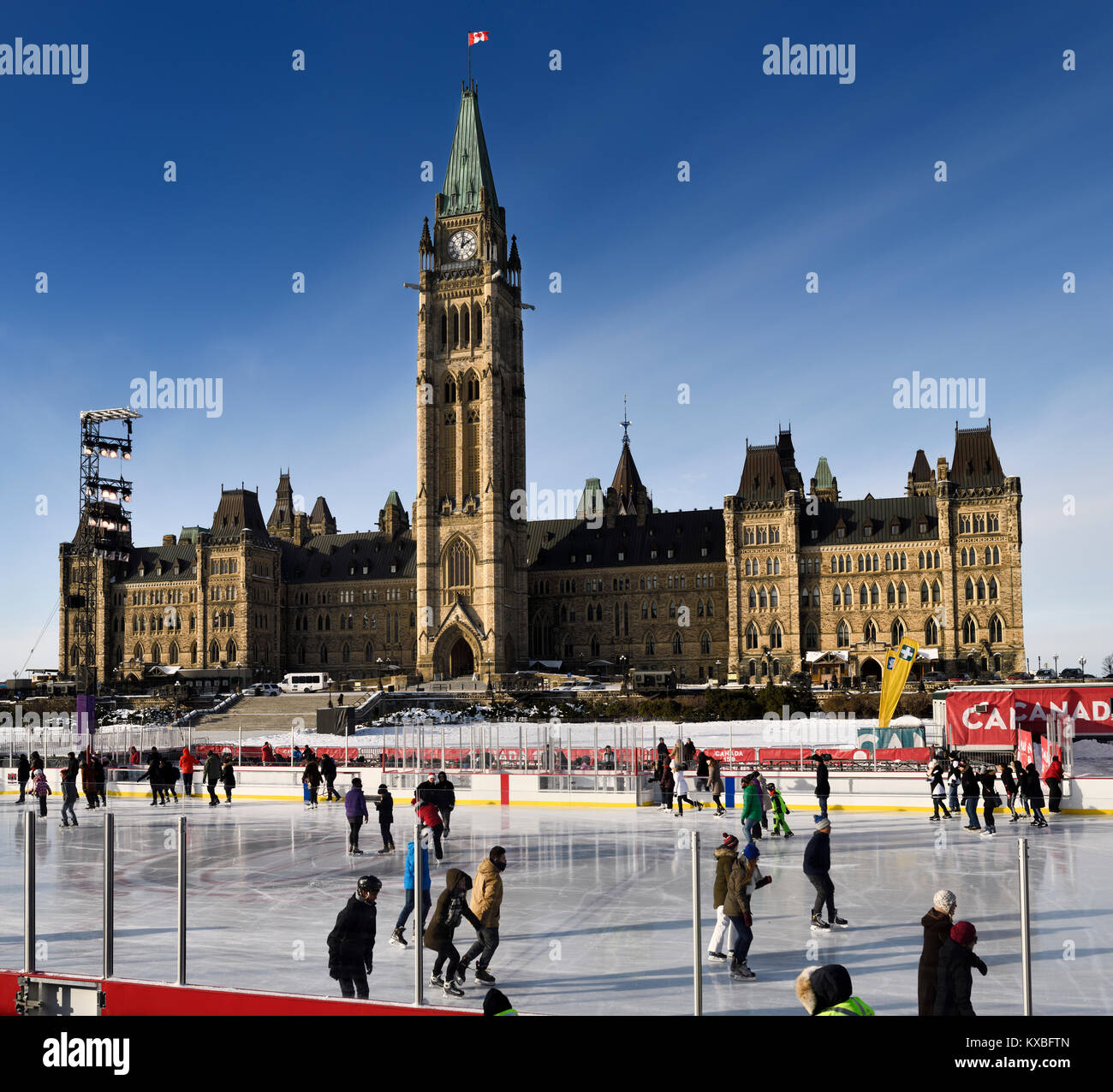 Parliament Hill Centre Block Peace Tower with afternoon sun on skaters on the Canada 150 Rink outdoors in winter Stock Photo