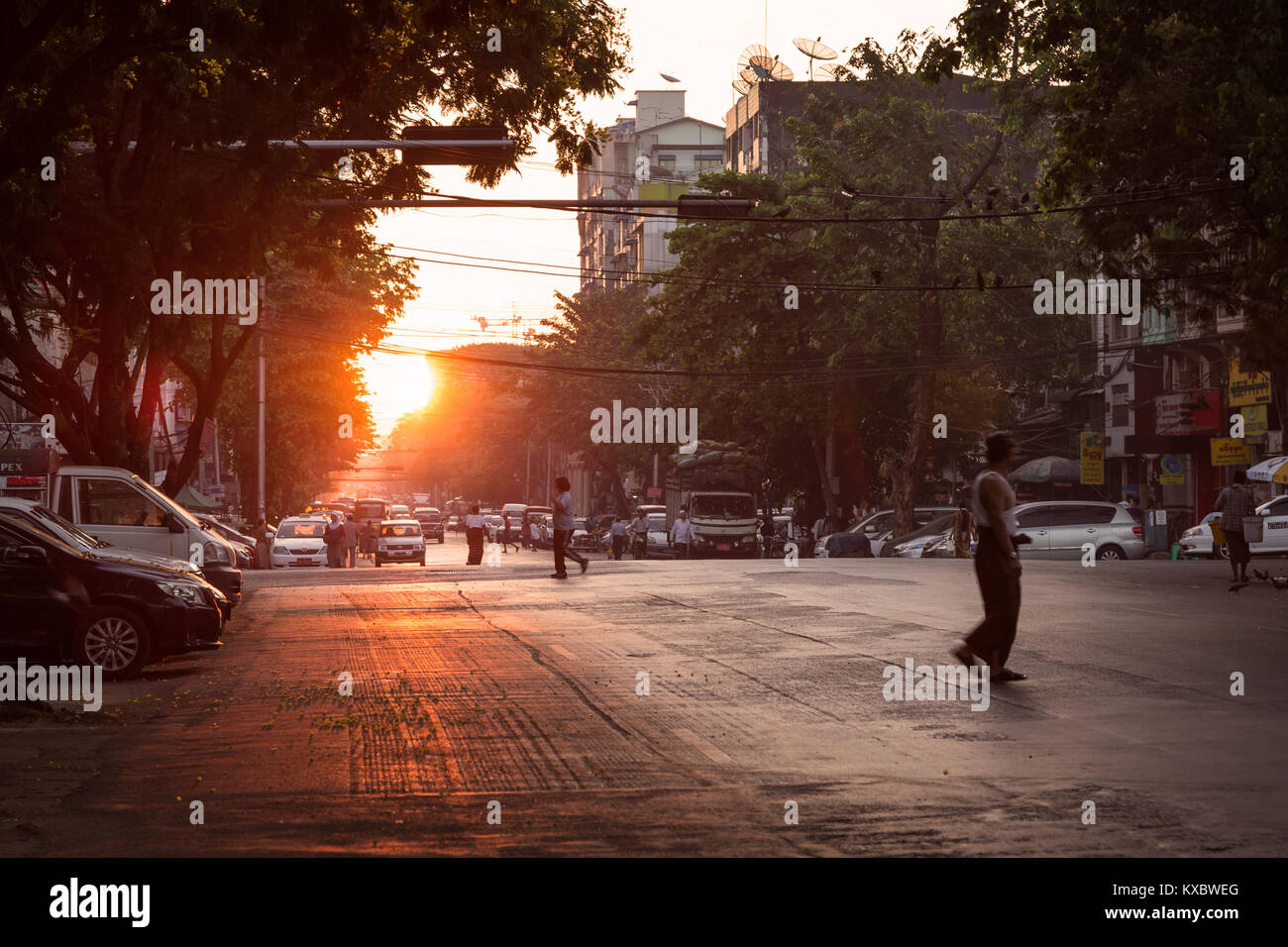 Some people and traffic on the Merchant Road at the downtown in Yangon (Rangoon), Myanmar (Burma), at sunrise. Stock Photo