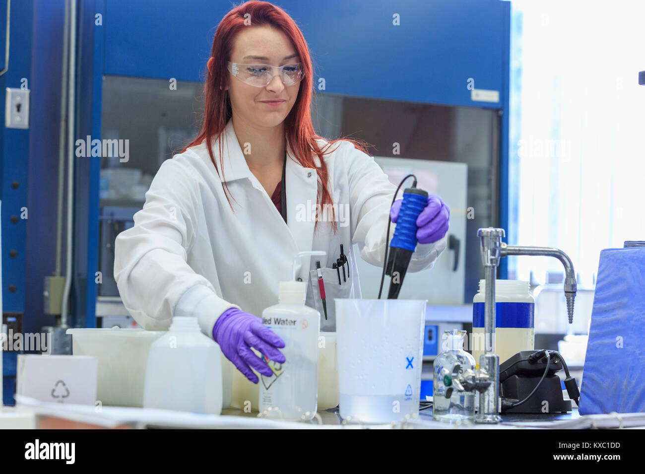 lab chemist adding distilled water while measuring ph stock image