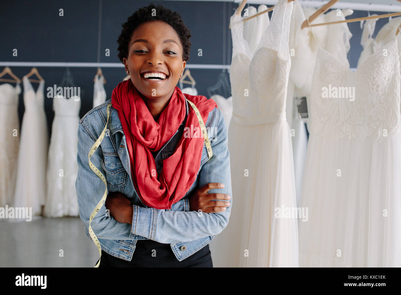 Portrait of african female bridal store owner standing with her arms crossed and smiling. Woman tailor standing - Stock Image