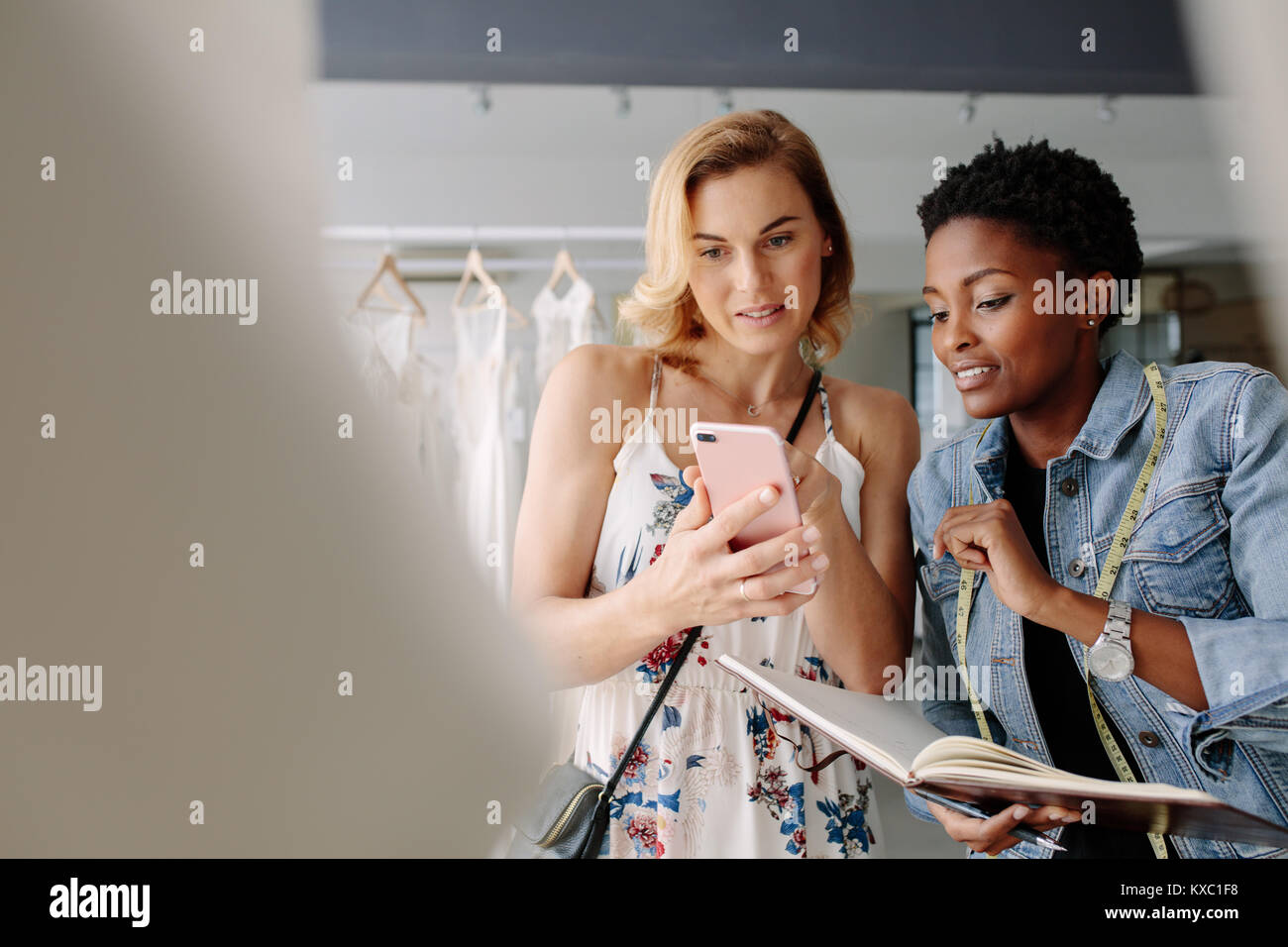 Woman showing a bridal wear pattern on her mobile phone to bridal dress tailor. Bride shopping for wedding outfit - Stock Image
