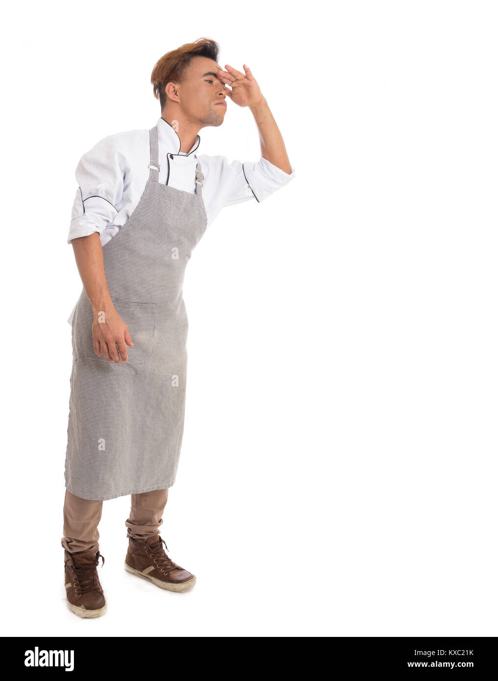 Man puts hand on the forehead and looks for something. Young cook wears apron. Full body image. Isolated on white - Stock Image