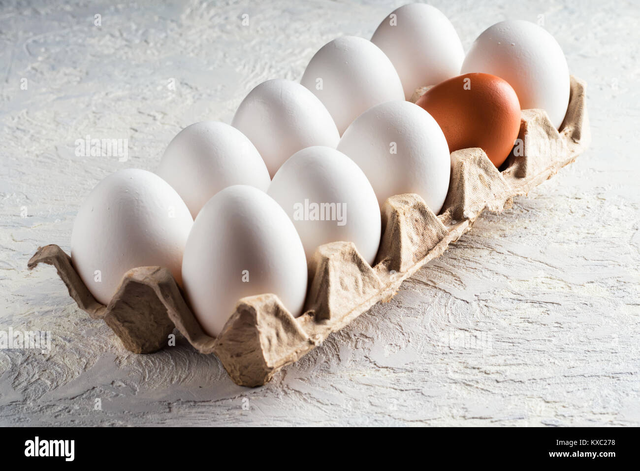 Pack egg white and one beige brown Concept harmful unnatural different other racism  - Stock Image