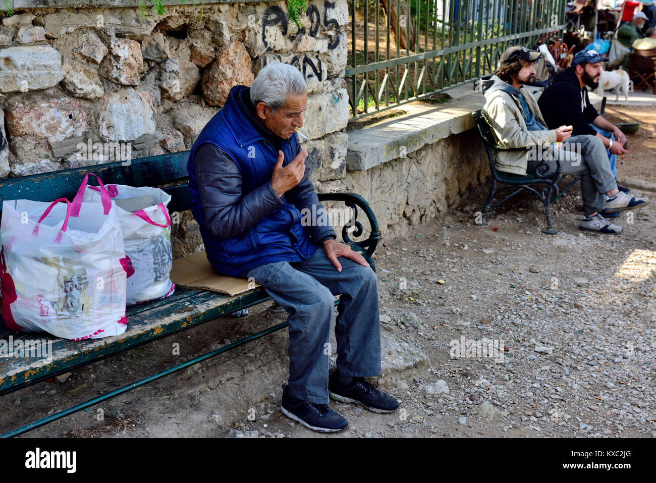 Older Greek man relaxing, sitting outside on bench with shopping bags, Athens, Greece Stock Photo