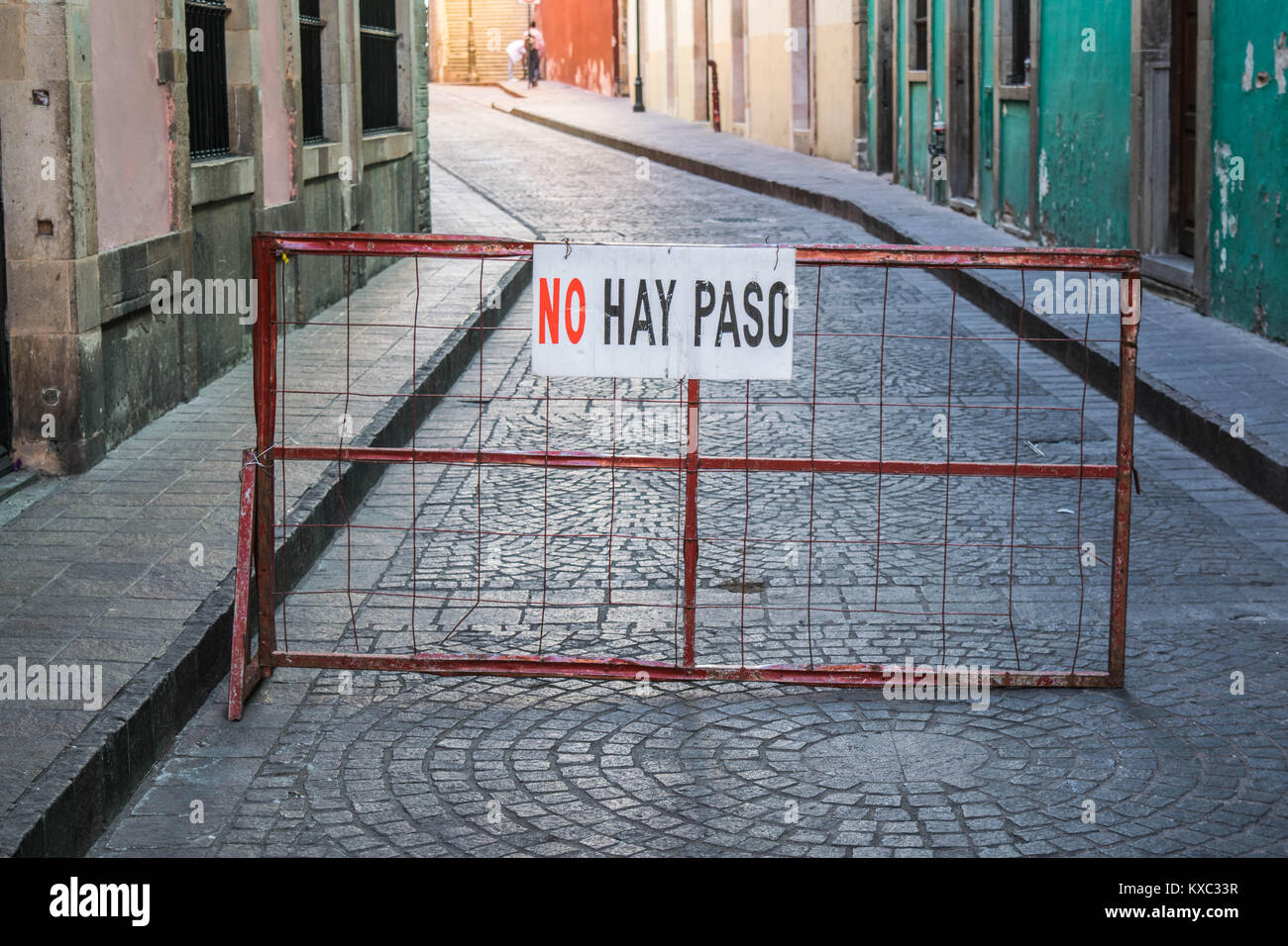 A red iron gate with a no passing sign, blocking the entrance to a cobblestone street with the bottom portion of - Stock Image
