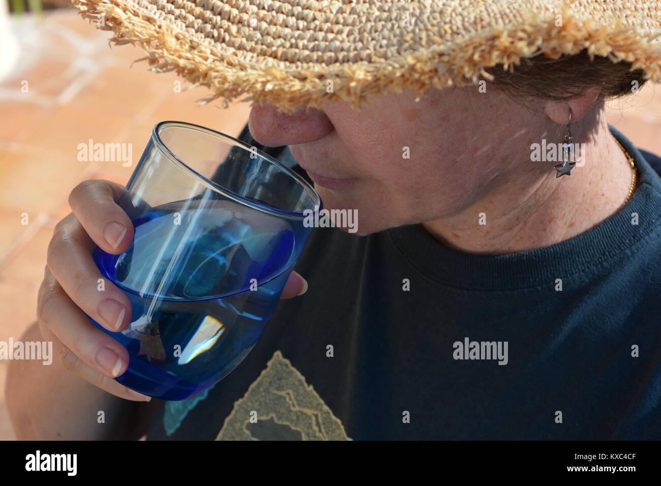 Woman outdoors, wearing a straw hat and drinking a glass of water - Stock Image