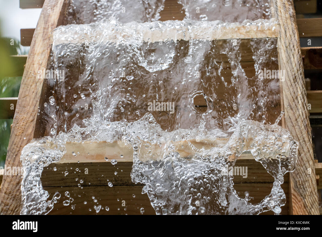 The blades of mill wheel rotates under a stream of water, close up view, open air museum. - Stock Image