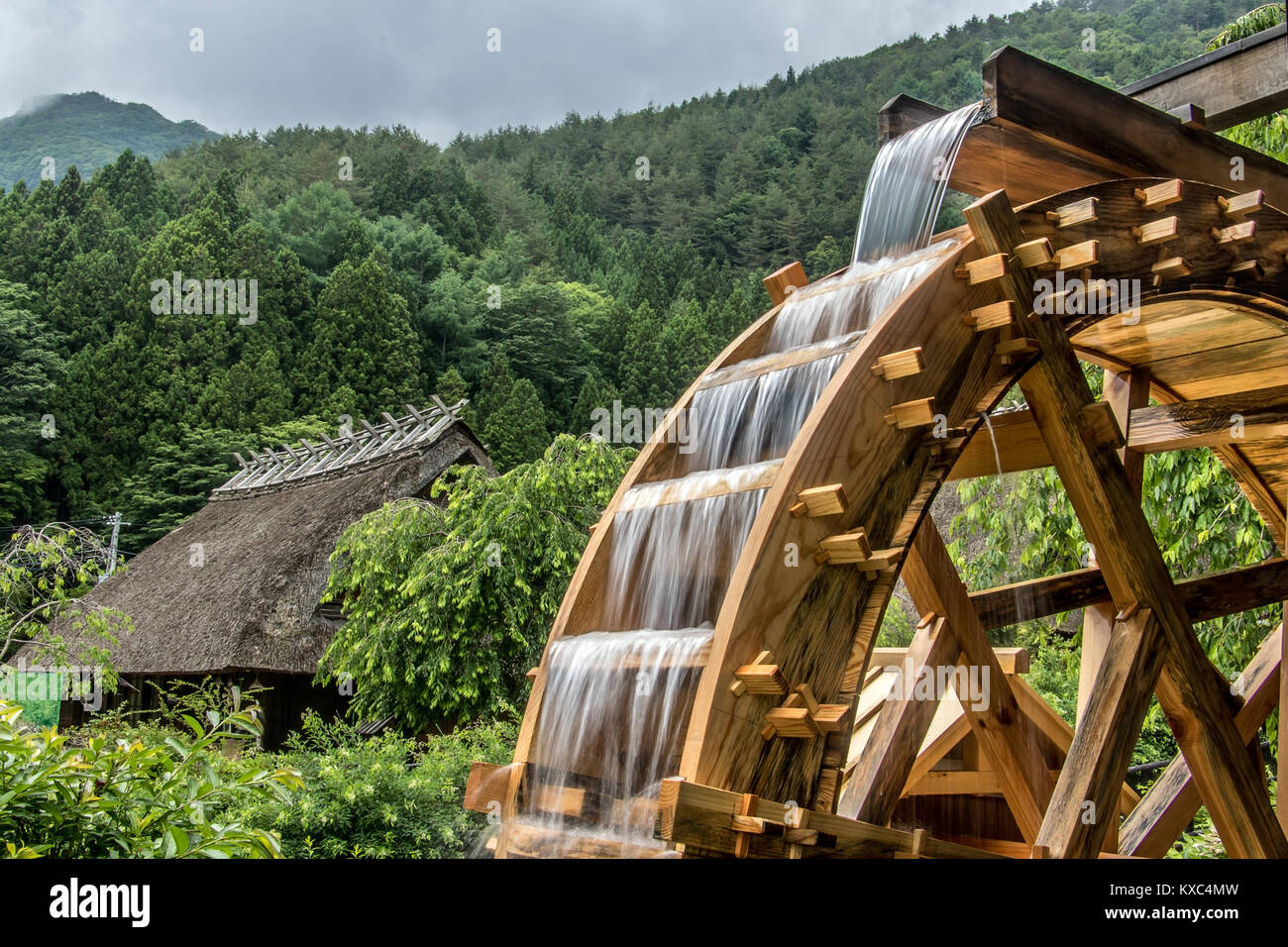 The mill wheel rotates under a stream of water, open air museum at village with traditional thatched roofed houses - Stock Image