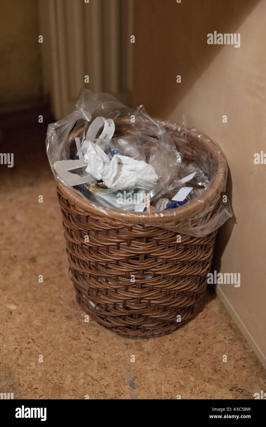 A Wicker Office Waste Paper Bin Full Of Rubbish Of All Sorts   Stock Image