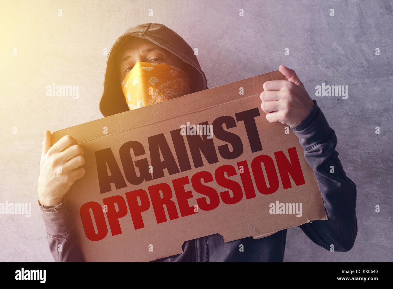 Activist protesting against oppression, hooded male person with scarf over face holding a banner with statement. - Stock Image