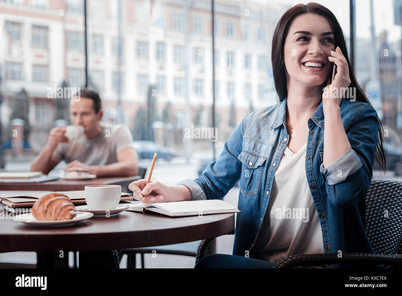 Happy female person making notes - Stock Image