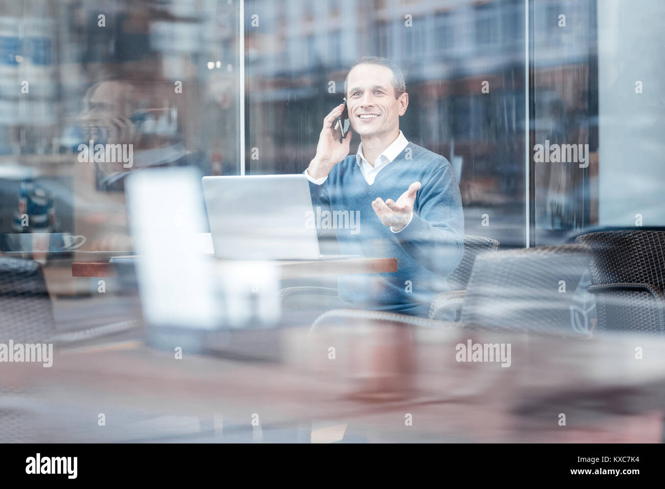 Positive delighted businessman having telephone talk - Stock Image