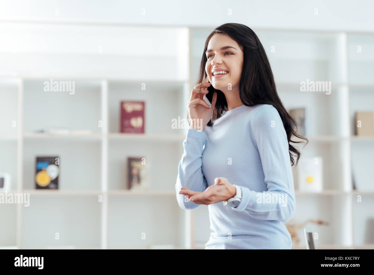 Cheerful cute woman answering call  - Stock Image
